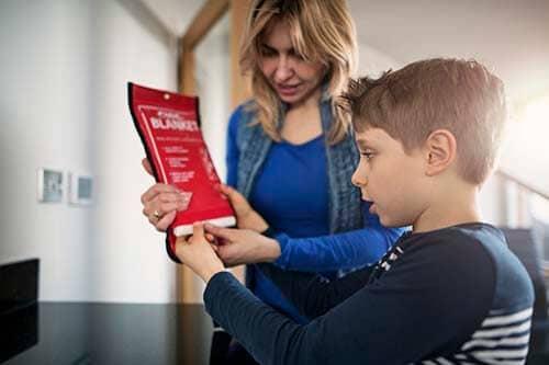mum-teaching-son-fire-safety-blanket-in-kitchen