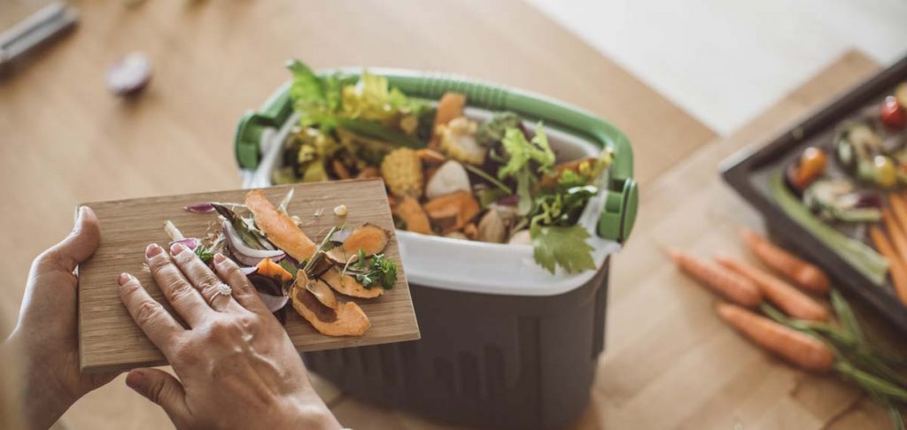 vegetables-being-scraped-into-environmentally-friendly-compost-bin